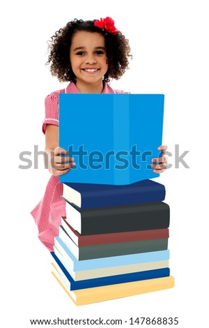 Girl reading a book from among pile of books - stock photo