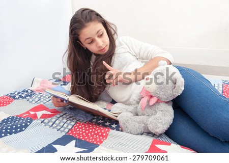 Girl reading a book her teddy bear - stock photo