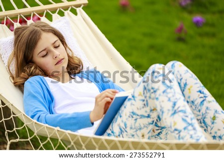 Girl reading a book in a hammock in the garden - stock photo