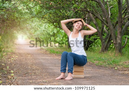 girl reading a book in the park - stock photo