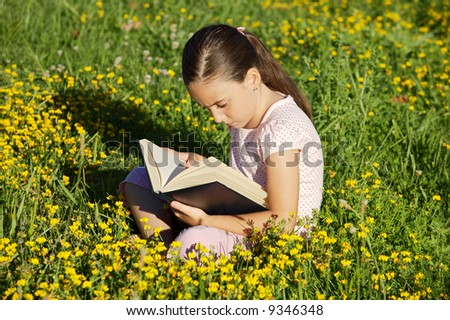 Girl reading a book on the grass - stock photo