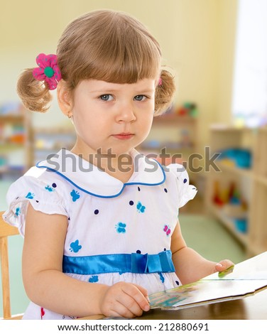 Girl reading a book while sitting at table.The concept of a child's learning and development. - stock photo
