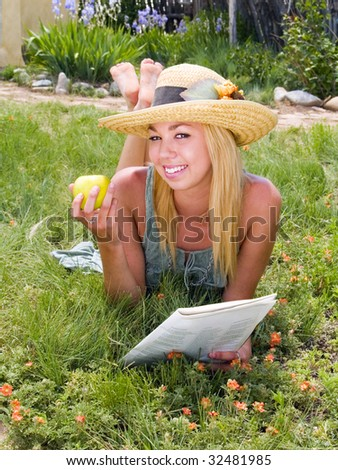 Girl reading a magazine and eating an apple in a garden