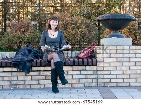 Girl reading a magazine on a park bench - stock photo