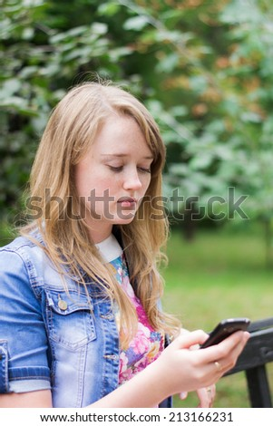 girl reading a message on the phone in the park - stock photo