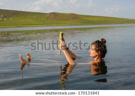 Girl reading a newspaper and floats in salt lake - stock photo