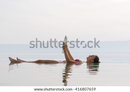 girl reading a newspaper floating in the waters of the Dead Sea - stock photo