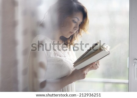 girl reading at the window