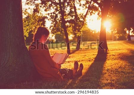 girl reading book at park in summer sunset light - stock photo