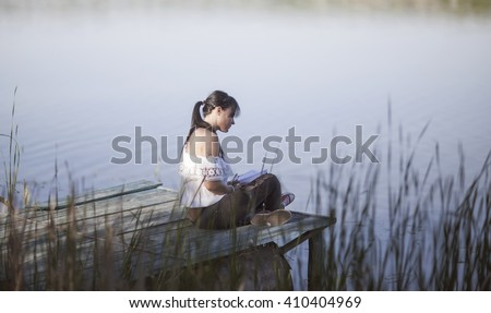 Girl Reading Book by the Lake