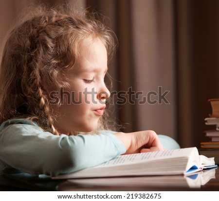 Girl reading book. Child education - stock photo