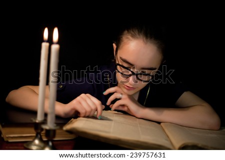 Girl reading book in dark library with candles