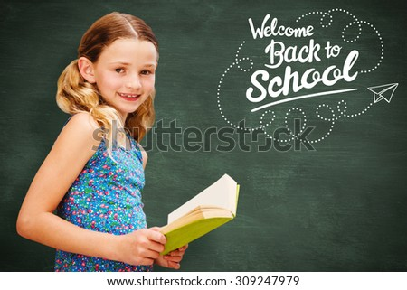 Girl reading book in library against green chalkboard