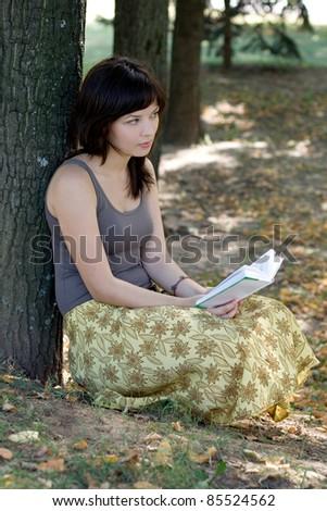 Girl reading book in park - stock photo