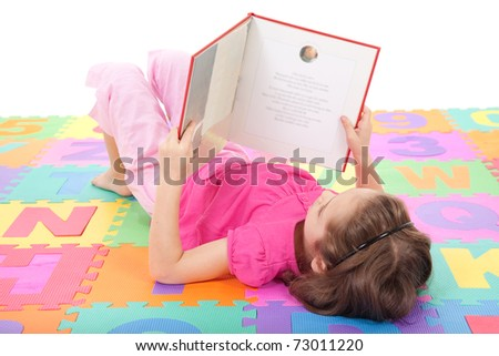 Girl reading book on alphabet letters floor mat. Isolated on white. - stock photo