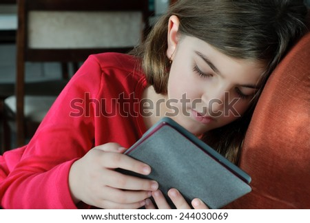 Girl Reading Book on E-Reader Stock Photo - stock photo