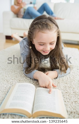 Girl reading book on the carpet with her mother reading the newspaper