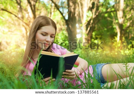 Girl reading book, while lying in the grass at park