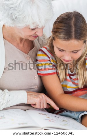 Girl reading book with granny on the couch - stock photo
