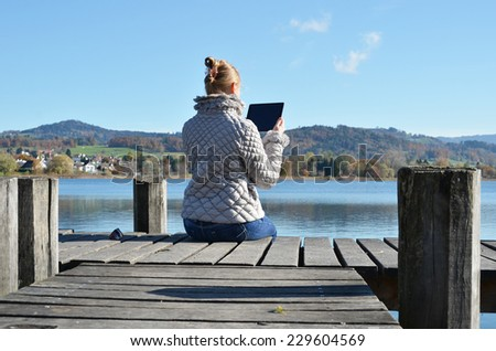 Girl reading from a tablet on the wooden jetty against a lake. Switzerland - stock photo