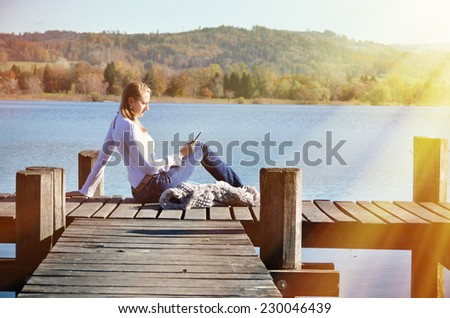 Girl reading from a tablet on the wooden jetty against a lake. Switzerland
