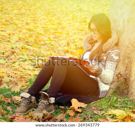 Girl reading in nature - stock photo