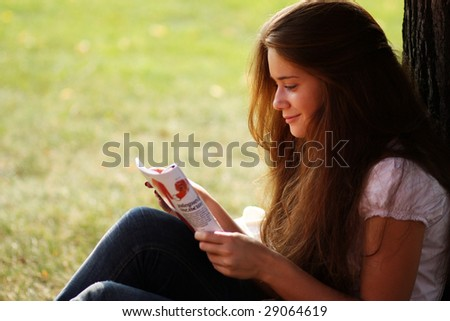 girl reading magazine in a park