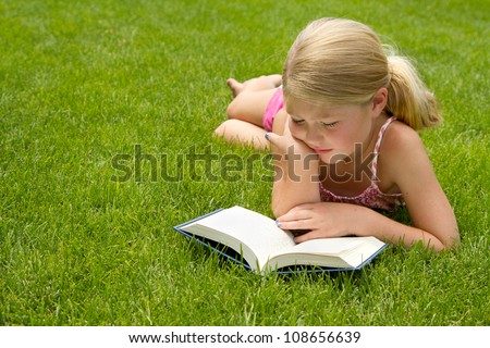 Girl reading outdoors in the grass - stock photo