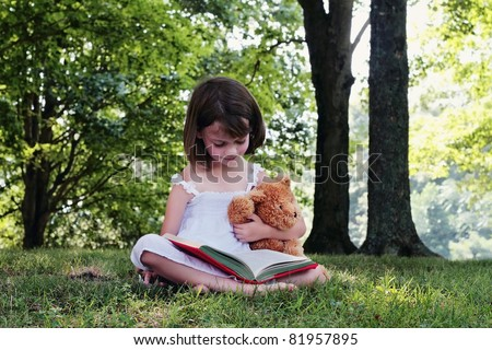 Girl reading outdoors to her little teddy bear. - stock photo