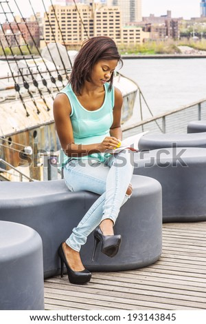 Girl Reading Outside. Wearing a green tank top, blue fashionable jeans, a young pretty woman is sitting on the deck in a harbor, crossing legs, looking down, reading a book on her laptop,  - stock photo