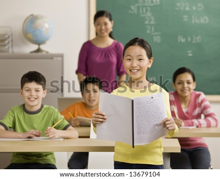 Girl reading report to classmates - stock photo