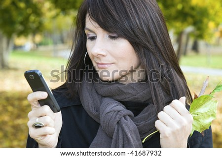 Girl reading text message in colorful park. - stock photo