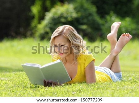Girl reading the book. Blonde beautiful young woman with book lying on the grass. Outdoor. Sunny day. Back to school - stock photo