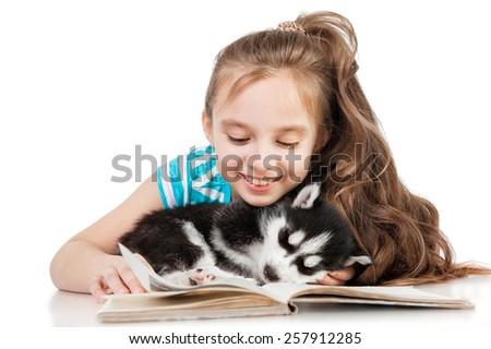 Girl reading with a puppy husky - stock photo