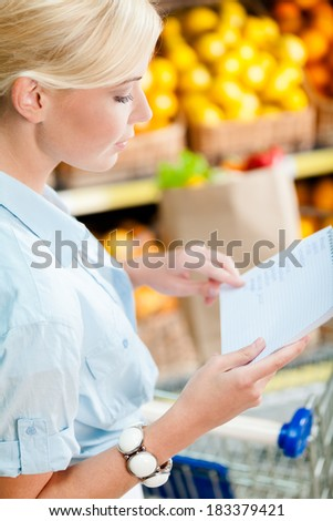 Girl reads shopping list near the heap of fruits lying in the braided baskets in the market