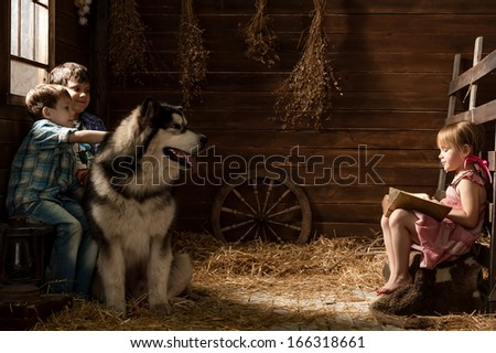 Girl reads the book to his brothers and a dog in a stable - stock photo