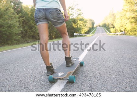 Girl ready to ride on a longboard.