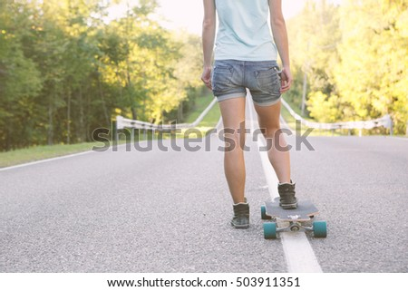 Girl ready to ride on a longboard. Toned Image.