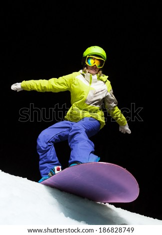 Girl ready to slide with snowboard at night - stock photo