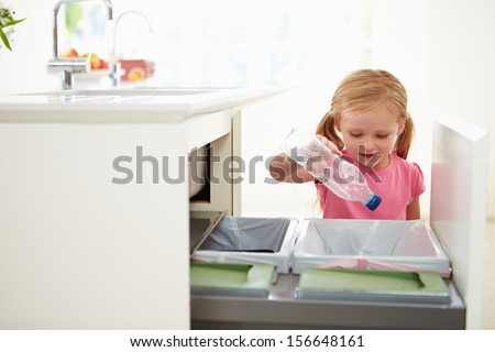 Girl Recycling Kitchen Waste In Bin - stock photo