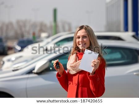 Girl red coat holds the keys and form. Buying a car - stock photo
