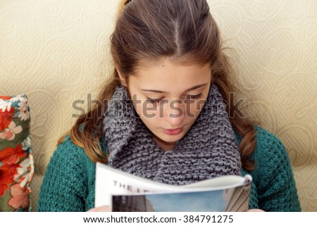Girl relaxes by reading a magazine