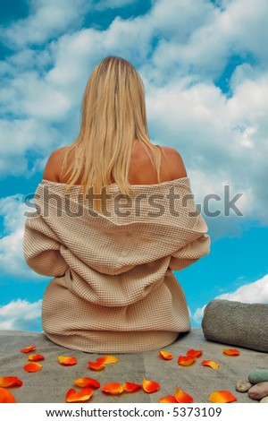 Girl relaxing after day in spa center and looking in beautyfull sky with clouds. - stock photo
