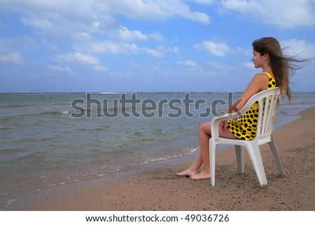 Girl relaxing in  chair at resort sea beach