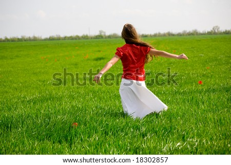 Girl relaxing in grass. It's windy and sunny. Back shot. - stock photo