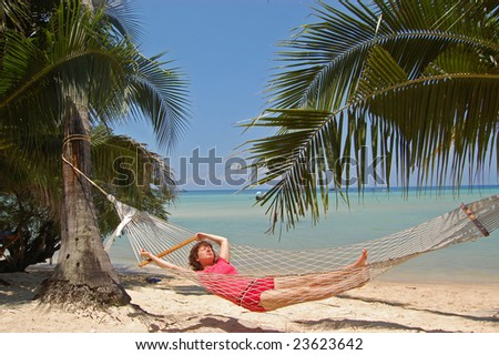 Girl relaxing in  hammock on beach, tropical vacation - stock photo