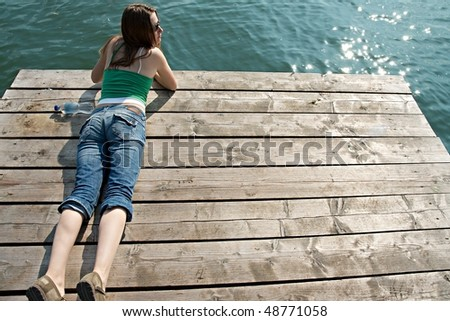 Girl relaxing on a pier at a lake in summer