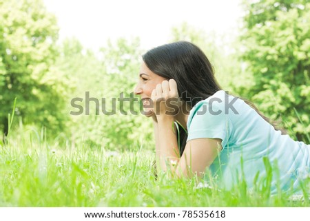 Girl relaxing on green grass. - stock photo