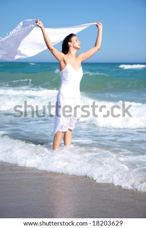 Girl relaxing on ocean beach with tissue scarf - stock photo