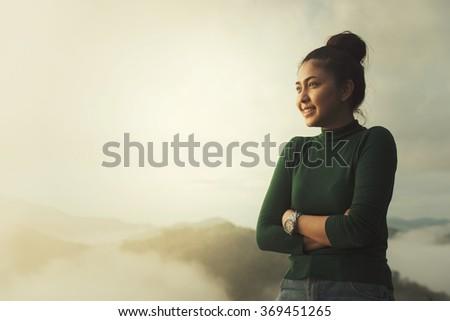 Girl relaxing on the top of mountain enjoying nature. - stock photo